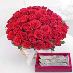 Astounding Red Roses with yummy Kaju Barfi to Bakaram